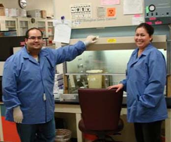 Two Microbiology Techs in front of a biosafety cabinet