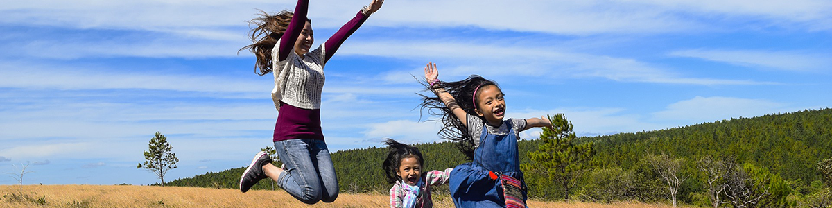 Three girls smiling and jumping in a field.