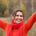 A woman in a sweater smiles broadly while outside during fall.