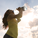 A woman drinks water in the sun.