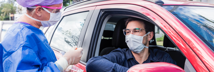 A patient wearing a mask goes through a drive thru testing site.