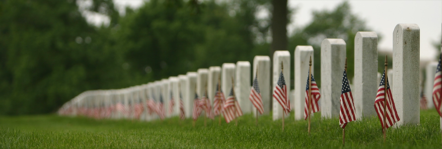 A row of tombstones with small American flags stuck in the dirt in front of them.
