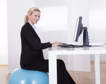 Woman working at desk sitting on ball